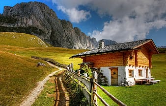 Brown wooden house near mountain at cloudy sky