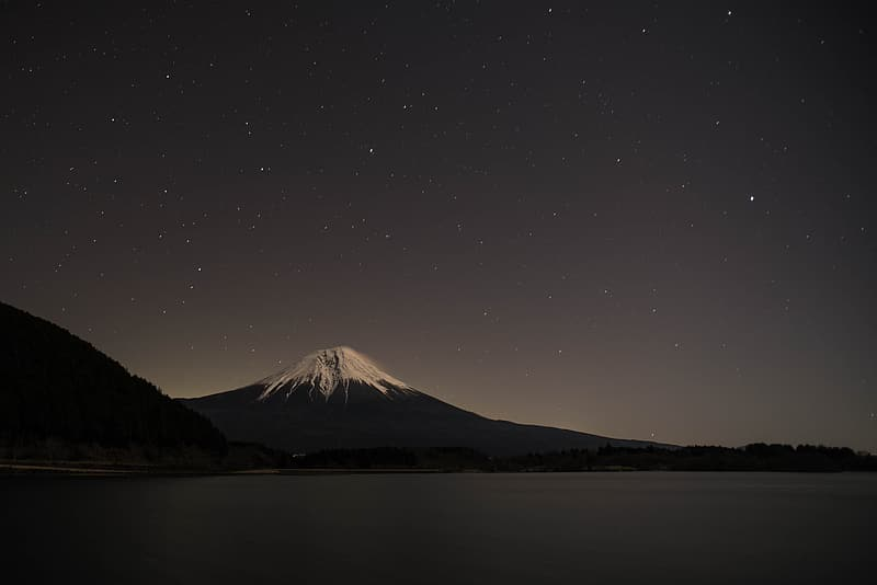 Photography of mountain near body of water during nighttime