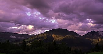 Black mountains under purple clouds