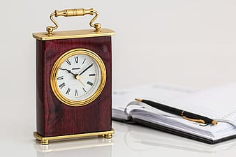 Brown and gold table clock showing 10:10