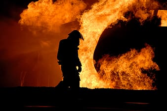 Silhouette of firefighter in front of flame photo