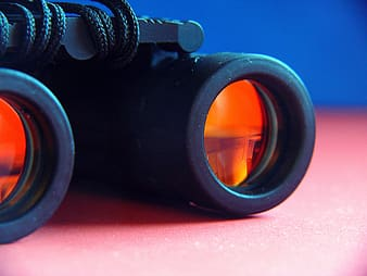 Selective focus photography of black and orange binoculars on pink surface