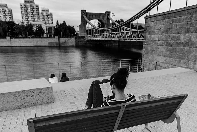 Woman sitting on bench while reading book in front of body of water grayscale photo