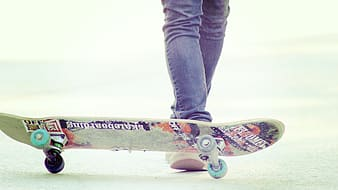 Person wearing blue jeans with skateboard