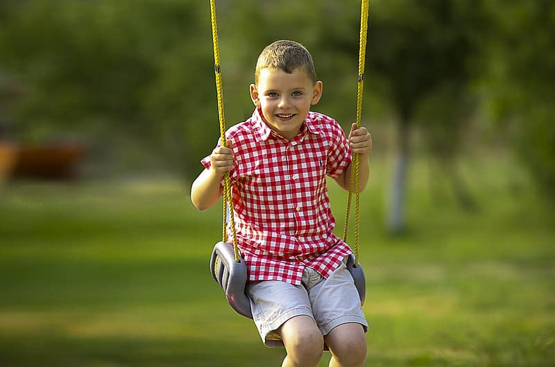 Smiling boy sitting on gray swing chair