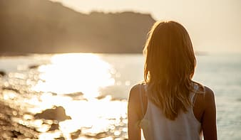 Woman in white tank top standing on beach during sunset