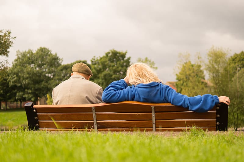 Man and woman sitting on bench during daytime