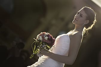 Woman in white strapless wedding dress holding flower bouquet in hand