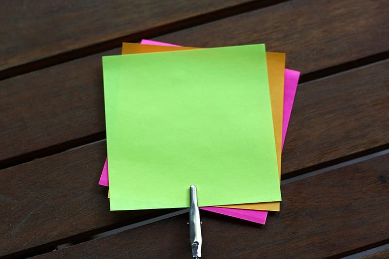 Sticky notes on brown wooden surface