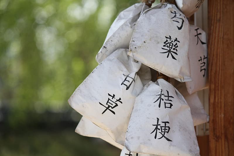 White-and-black kanji script-printed paper bags hanged on wall