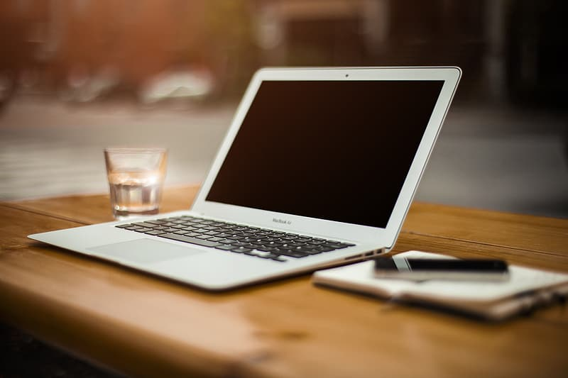 Black and gray laptop computer, MacBook beside drinking glass on wooden table