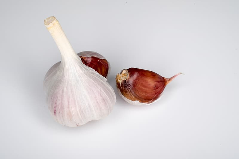 Two garlic bulb on white surface