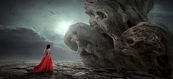 Woman in red dress standing on rock formation during daytime