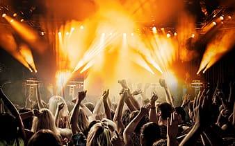 People raising hands infront of stage with band playing