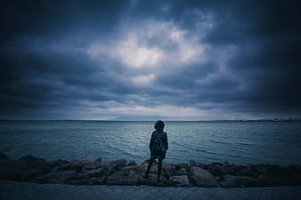 Woman in black dress standing on rock near sea under cloudy sky during daytime