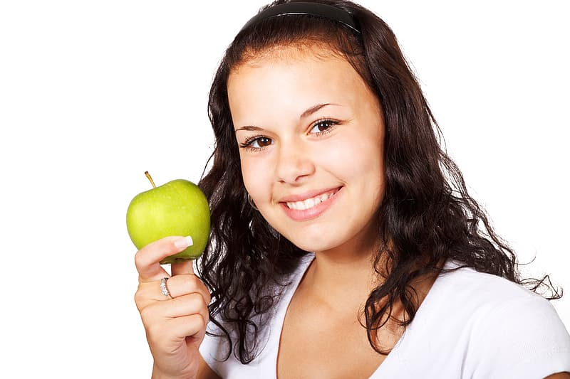 Woman in white shirt holding green apple while smiling