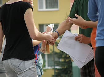Person holding white paper shaking hands with person in black top