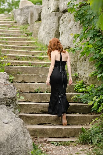 Woman in black dress standing on staircase