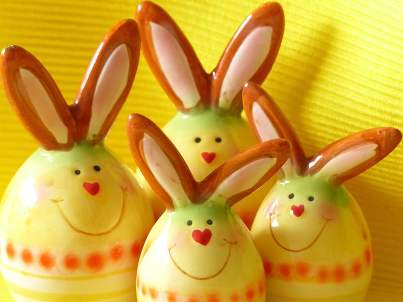 Four yellow-and-brown ceramic rabbit figurines