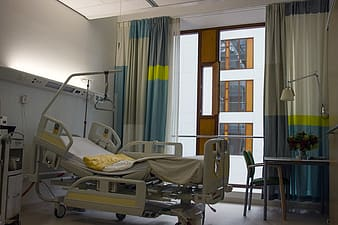 Gray hospital bed near blue and gray window curtain inside room