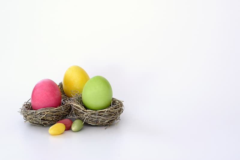 Pink, yellow, and green Easter egg on brown nest