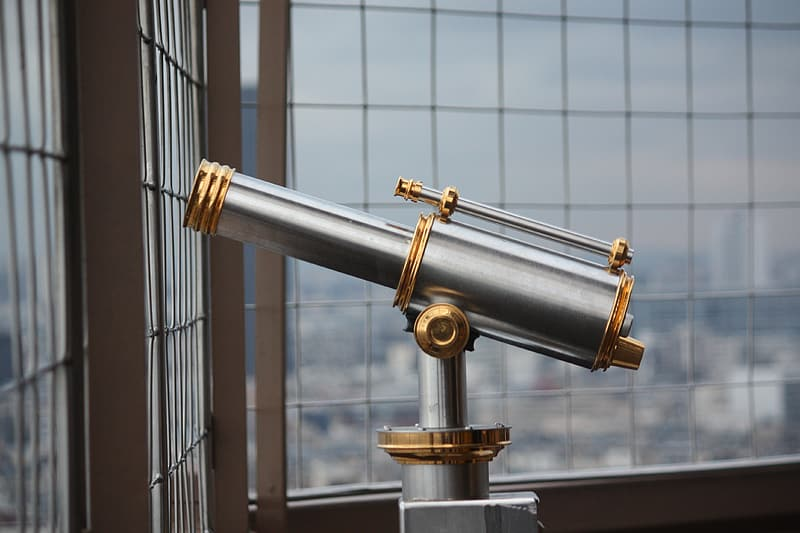 Gold and silver telescope in front of glass window