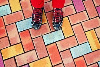 Person in red pants and black and white sneakers standing on brick floor