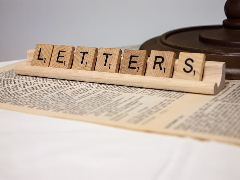 Brown wooden scrabble tiles displaying letters