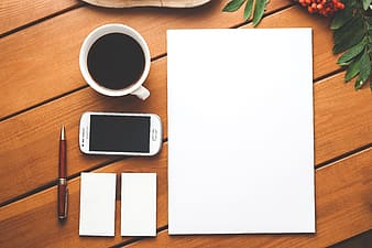 High angle photo of white paper, white Samsung Galaxy Android smartphone, white ceramic mug filled with tea, red fountain pen and two white mini papers