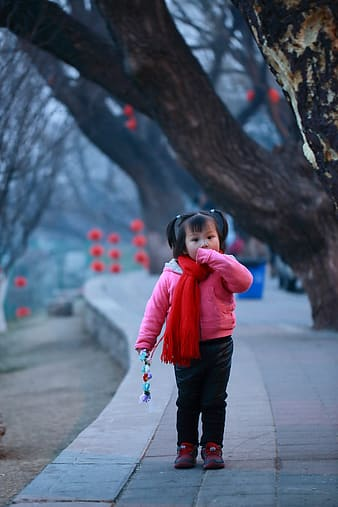 Selective focus photo of girl standing on green pathway near the brown tree