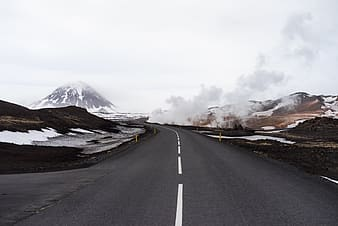 Gray asphalt road surrounded by snow and fog