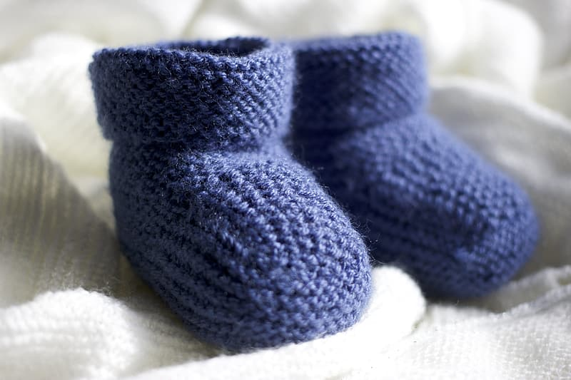 Pair of blue bootees on white textile