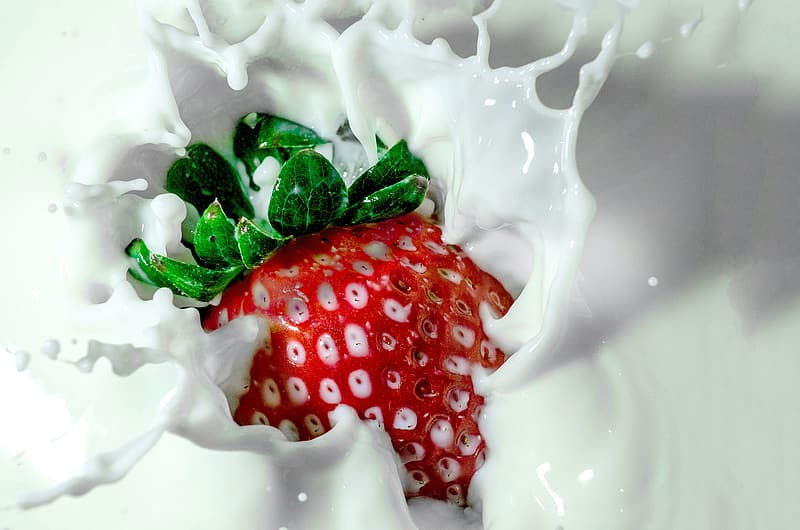 Timelapse photography of strawberry tossed into milk