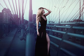 Person taking photo of blonde haired woman in black plunging neckline sleeveless dress in tilt shift photography