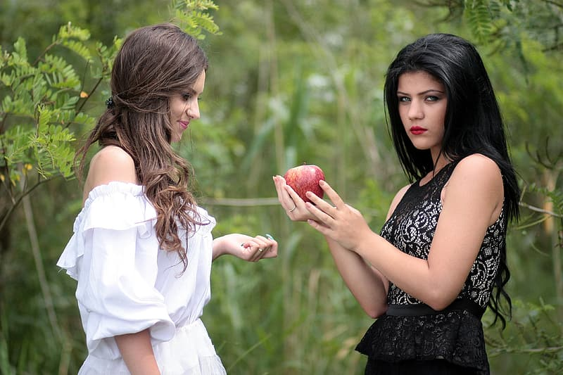 Two women in black and red dresses near green trees at daytime