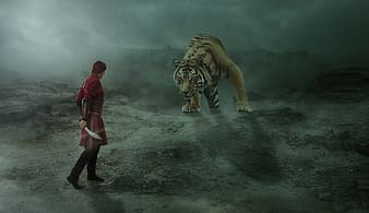 Man in red jacket standing beside tiger