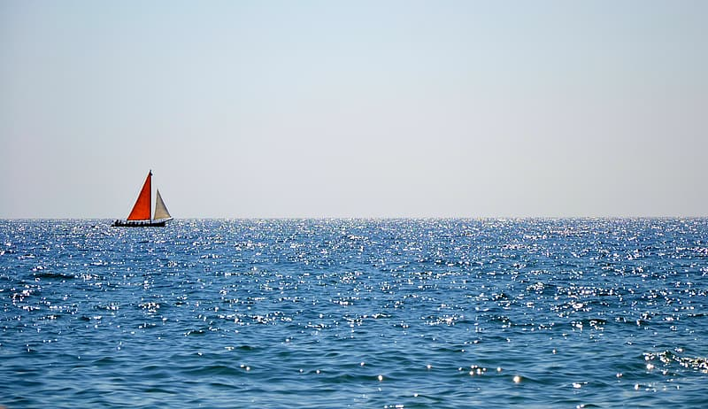 Red and white sailing boat on body of water photography