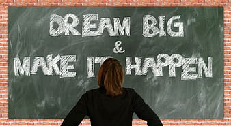 Person in black long-sleeved shirt standing front of Dream Big & Make It Happen text