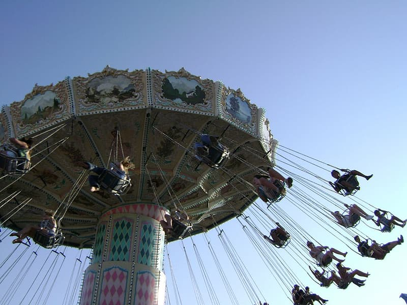 People riding on white and blue ferris wheel during daytime