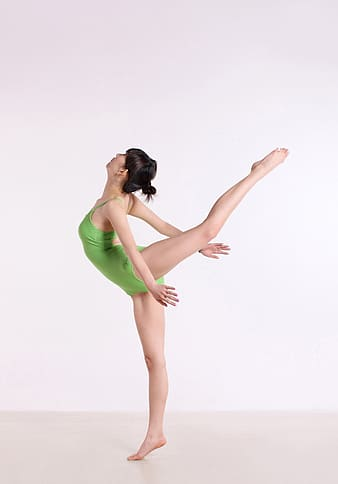Woman wearing green bodysuit exercising in white painted room