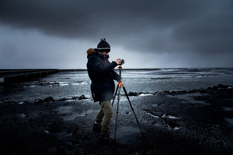Man in black jacket and black hat standing on rocky shore under gray cloudy sky