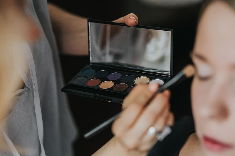 Woman holding makeup brush and eyeshadow palette