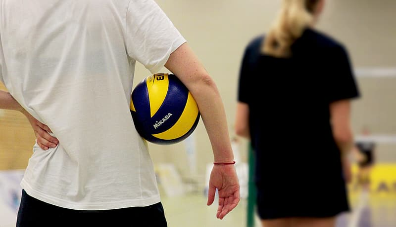 Person in white t-shirt holding yellow and blue volleyball
