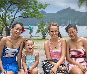 Three woman and girl sitting near body of water