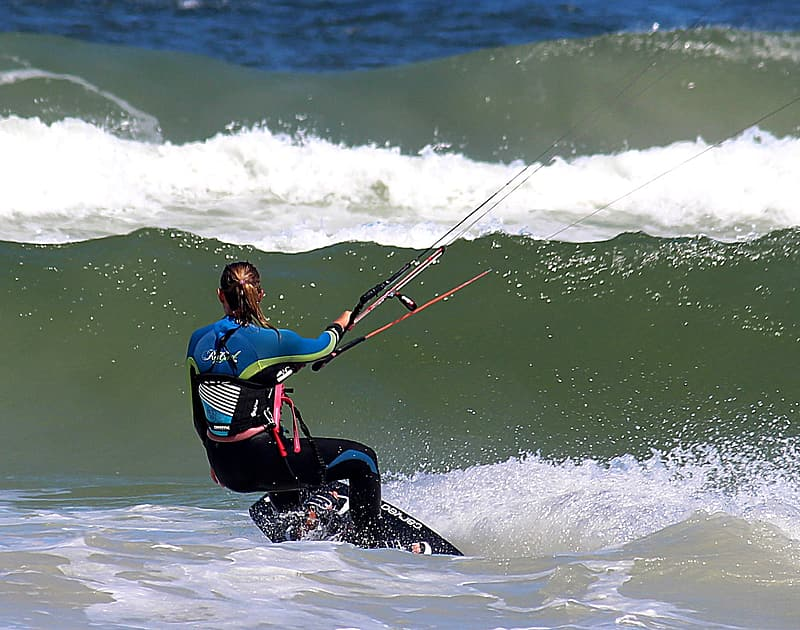 Man in blue and red shirt surfing on sea waves during daytime