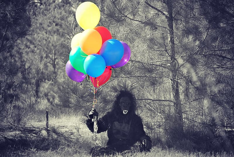 Person in black gorilla costume holding balloons in forest