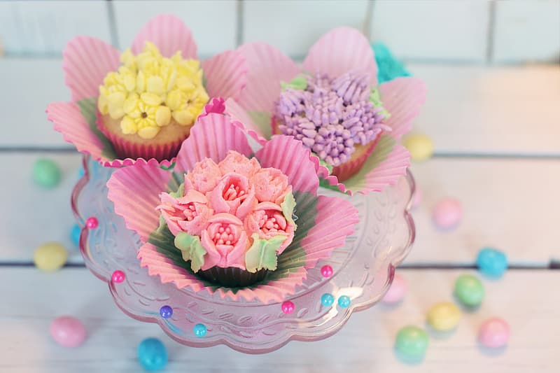 Three assorted cupcakes on clear glass bowl