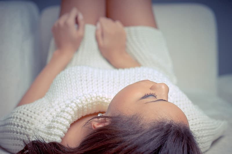 Woman in white knitted dress lying on bed