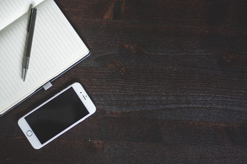 Silver iphone 6 beside white ruled paper