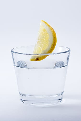 Photo of lemon about to drop on glass of water